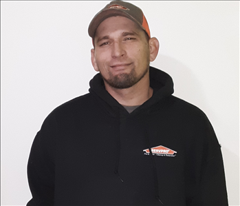 Male employee standing in front of a white back ground wearing a black hooded sweatshirt and a gray and orange  ball cap