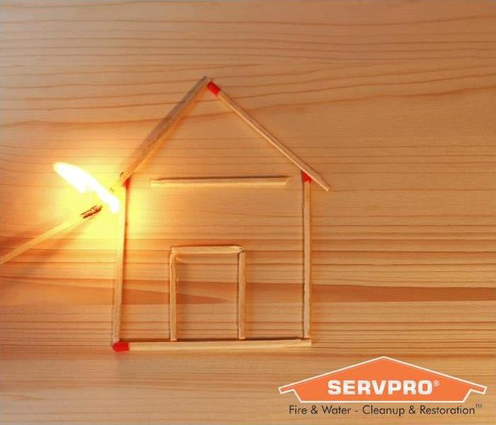 Match sticks in the shape of a house near a flame.